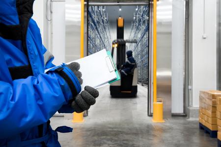 Mano de trabajador con portapapeles control de mercancías en la sala de congelación o almacén