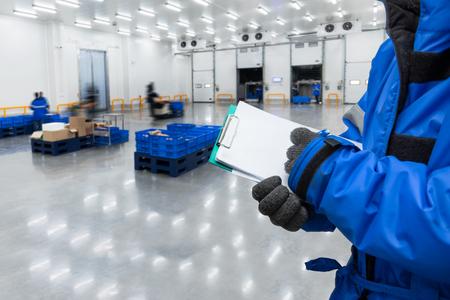 Hand van werknemer met klembord die kant-en-klaarmaaltijden in het magazijn controleert., Import- en exportbeheersysteem voor klantenserviceconcept.