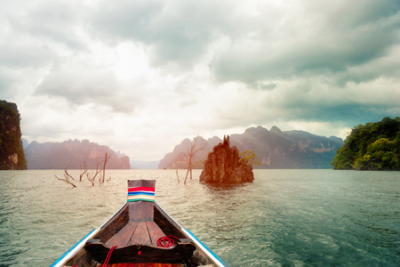 Long-tailed boat floating on the asia lake in the among the islands with mountains in background