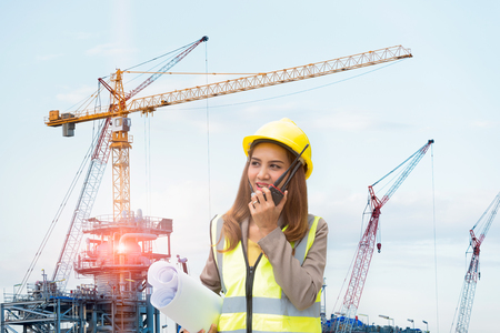 Engineer woman talking a walkie-talkie for communication with supplier and holding drawing paper in the construction site