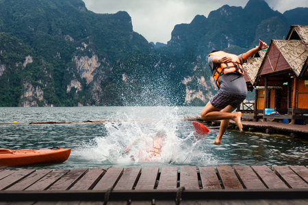 Young man jumping into the lake from the jetty.  Activity relaxing and Adventure trips on summer holidays. relax your way concept.