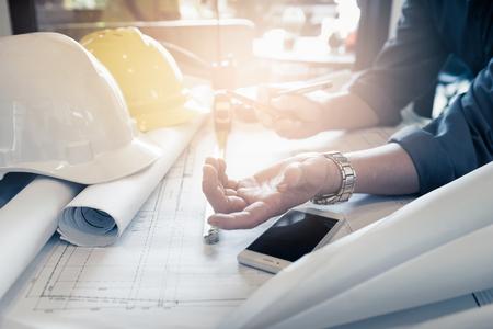 Cerrar la mano del ingeniero civil con la discusión de planos de dibujo en la oficina Foto de archivo