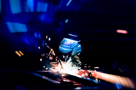 Welding at the industrial factory for steel production heavy industrial. add grain filter dark tone and motion for heavy work concept.