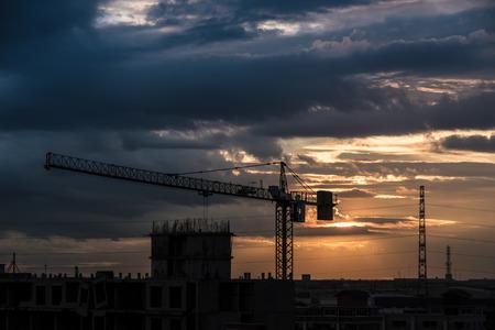 Vue sur la grue à tour dans la machine de construction un fond de ciel, surtout dans la pénombre.