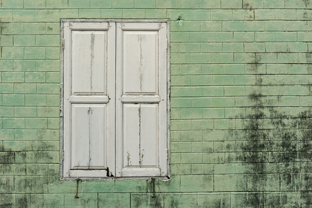 Old window with green wall is suitable for use as a background.