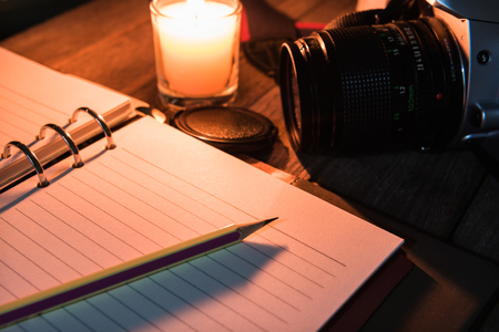 Diary open with pencil near the burning candle on table. Memories of life or travel concept  Selection focus to a pencil.