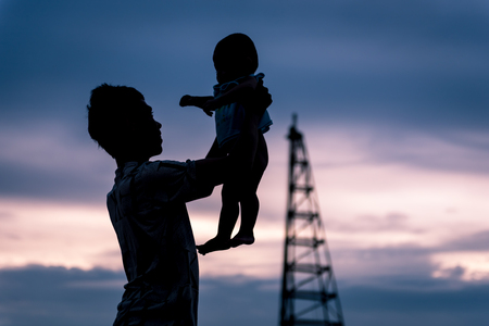 Father holds his child with love. silhouette on the sunset time