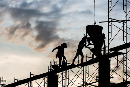 Silhouette of worker. Construction Building casting concrete work on scaffolding. Zdjęcie Seryjne