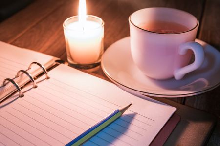 Diary open with pencil and hot drink near the burning candle with bright flame on table  Memories of life or novel writing concept  Selection focus to a pencil. Stockfoto