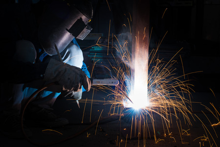 Welding skills training of welder with protective mask and welding steel metal part.