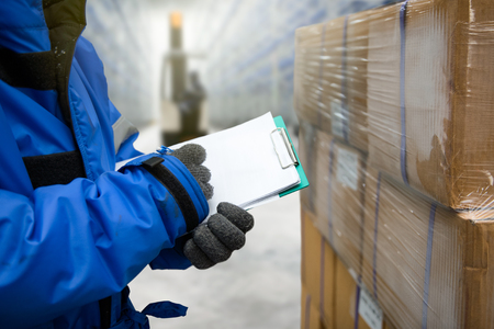 Close-up schieten hand van werknemer met klembord controleren van goederen in vrieskamer of magazijn