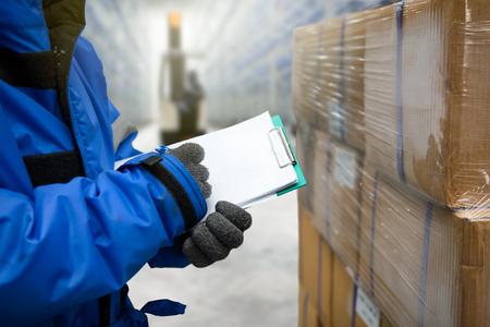 Primer tiro de mano de trabajador con portapapeles comprobando mercancías en la sala de congelación o almacén