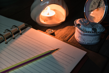 Diary open with pencil near the burning candle with bright flame on table  Memories of love concept  Selection focus to a pencil.