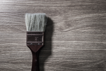 Paintbrush on wood background, Dark color tone.