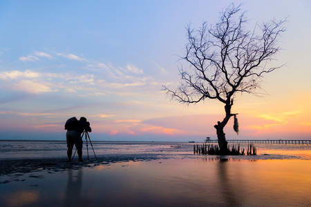 Man traveler photograph relaxing with beautiful sunset and silhouettes of trees on the lake location