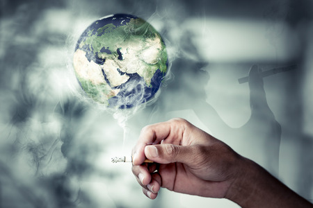 Hand of people holding the tobacco with smoke Burning the earth., World No Tobacco Day Concept and For Centers for Disease Control (CDC)., Protecting people. Elements of this image furnished by NASA.