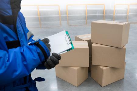 Gros plan de la main de prise de vue du QC. travailleur avec presse-papiers vérifiant les boîtes d'emballage de marchandises dans l'entrepôt de la chambre froide., concept d'entreposage frigorifique des aliments