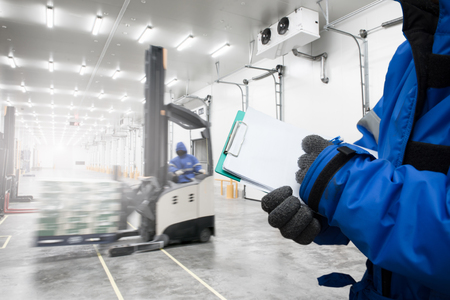 Hand des Arbeiters, der die Zwischenablage hält, die Waren im Gefrierraum oder im Lager mit dem Hintergrund eines Standstaplers hält, der zum Heben und Bewegen der Fertiggerichte verwendet wird