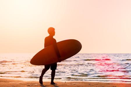 Silhouette junger Mann mit Surfbrett am Strand mit Sonnenlicht und Flare., Sommeraktivität der Menschen am Strandkonzept. Standard-Bild