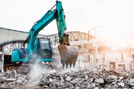 Máquina excavadora en sitio de construcción demoliendo edificio existente