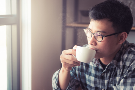 Asian young man drinking coffee in the cafe., How to lifestyle of young asian businessman in the weekend activity relaxing with the coffee. drinking concept. Banco de Imagens