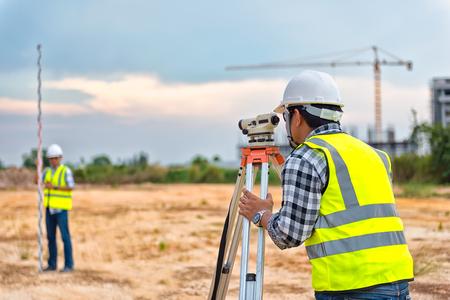 Landmeter apparatuur. De telescoop van de landmeter op de bouwplaats of landmeetkunde voor het maken van contourplannen is een grafische weergave van de ligging van het land vóór het opstarten van de bouwwerkzaamheden
