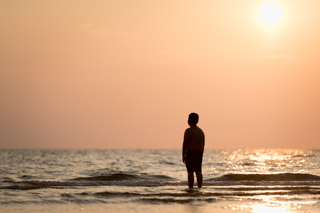 Silhouette of a lonely boy standing alone on the beach at sunset. Concept of lonely and hope of kids or moment of farewell