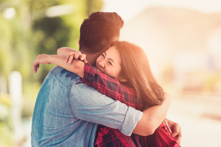 Young Couple Asian to happy hugging on street after arrival in summer with a warm sunlight background. Imagens