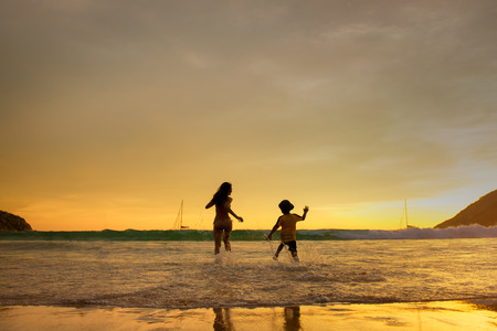 The couple of happy young people on the beach is running with children jumping in the on a background of sunset beach and sea 版權商用圖片