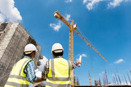 Discusión de ingenieros de construcción con arquitectos en el sitio de construcción o sitio de construcción de un edificio de gran altura