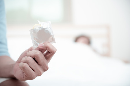 Close Up of a hand of the young man holding opening condom with a woman on the bed is background. Focus to a condom.  Best condom for protection