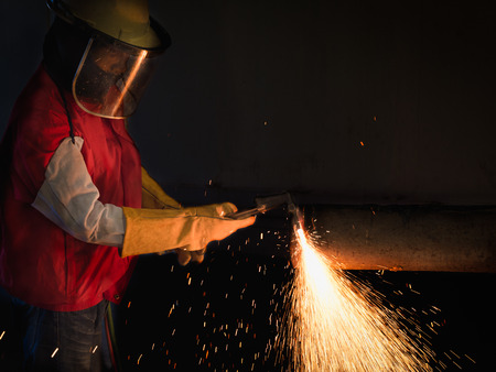 Jobs Of Professional worker.  Professional worker to cutting steel in the plan of construction site with Oxy-Propane cutting and mask for protection.