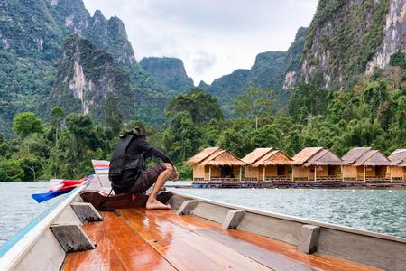 El hombre levantó las manos disfrutando del viaje de aventura de su vida flotando en un bote en el lago de Asia con casa flotante en el río del lago en atracciones naturales y montañas