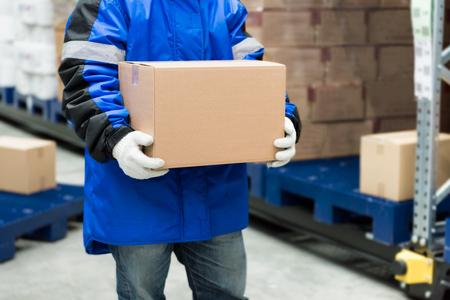 Travailleur transportant une boîte de marchandises dans un grand entrepôt congelé. Concept de système logistique d'exportation-importation