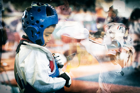 Taekwondo Asian kid with head guard. Double exposure another player during the tournament taekwondo kids in stadiums. Add old film filter and dust for feeling of former athlete history.