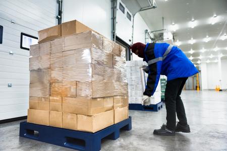 Plastikverpackungsrolle zum Verpacken beim Laden von Waren des Gefrierlagers. Lagerung für Fertiggerichte oder verzehrfertige Lebensmittel. Systemkonzept der Export-Import-Logistik.