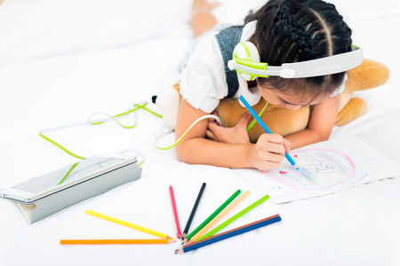 Asian little girl listen to music from tablet with green headphone while writing with colorful pencils on bed in the home. Education for kids and strengthens the imagination of children concept.