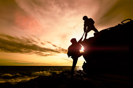 Silhouette of couple helping each other while climbing up on rocks beach in sunset. The concept of aid. Stock fotó