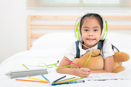 Portrait asian little girl listen to music from tablet with green headphone while writing with colorful pencils on bed. Education for kids and strengthens the imagination of children concept