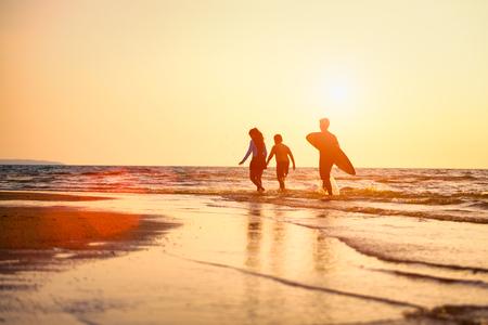 Silhouette junger Surfer mit Brüdern, die sie am Sonnenuntergangsstrand entspannen. Sommeraktivität von Menschen am Strandkonzept. Extremsportkonzept. Standard-Bild