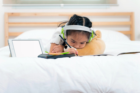 Asian little girl unhappy about the homework writing with pencils on bed while listen to music from tablet with green headphone. Education for kids and strengthens the imagination of children Banco de Imagens