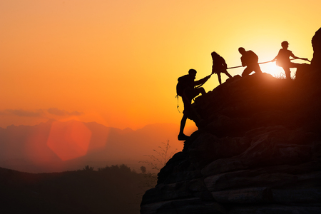 Silhouette of the climbing team helping each other while climbing up in a sunset. The concept of aid. Stock Photo
