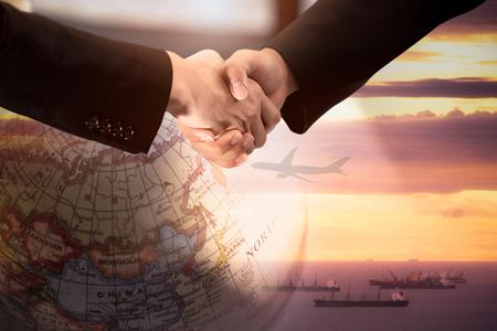 Stretta di mano dell'uomo d'affari per l'accordo dei partner logistici con l'immagine a doppia esposizione della mappa del mondo del globo e la spedizione.