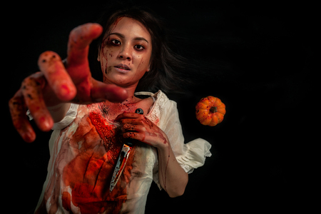Mental disorder of Asian girl with knife holding in her hand. Suffering most from suicidal thoughts concept. Horror photo for Halloween festival.