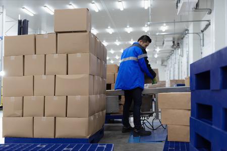 Empaque cajas de cinta transportadora en almacén o área de carga.