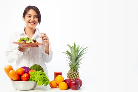 Asiatische junge Frau mit Salatgemüse mit frischem Obst und gesunder Ernährung auf dem Tisch.