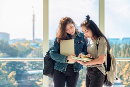 Dos estudiantes asiáticas discutiendo y señalando con el dedo a las notas en el libro para encontrar la respuesta correcta a su pregunta preparándose para el examen universitario. Vida de estudio y amistad.