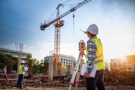 Equipo de agrimensor. El telescopio del agrimensor en el sitio de construcción o el levantamiento para hacer planos de contorno es una representación gráfica de la disposición del trabajo de construcción inicial de la tierra.