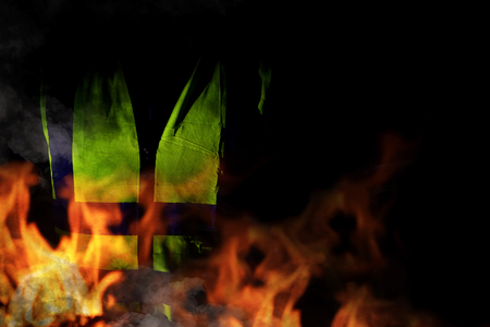 Yellow vests of protest with fire in France on black background. Protester news concept.