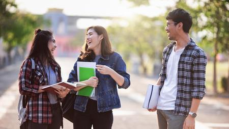 Tres estudiantes asiáticos becados sonríen y se divierten en el parque en la universidad después de aprender en el aula. Vida de estudio y concepto de amistad.